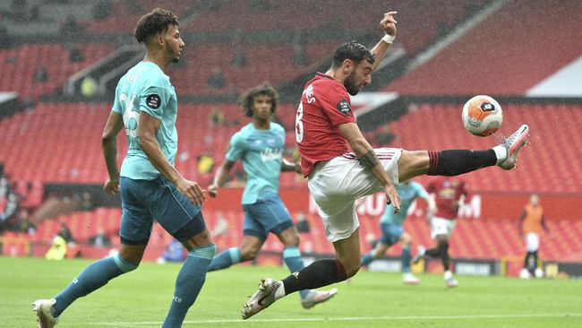 Manchester United's Bruno Fernandes, right, reaches for the ball while Bournemouth's Lloyd Kelly, left, defends during the English Premier League soccer match between Manchester United and Bournemouth at Old Trafford stadium in Manchester, England, Saturday, July 4, 2020. (Peter Powell/Pool via AP)