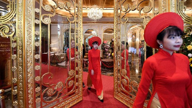 Staff wait to welcome guests in the lobby of the newly-inaugurated Dolce Hanoi Golden Lake hotel, the world's first gold-plated hotel, in Hanoi on July 2, 2020. (Photo by Manan VATSYAYANA / AFP)