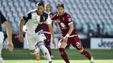Juventus' Rodrigo Bentancur, left, is challenged by Torino's Simone Verdi during the Serie A soccer match between Juventus and Torino, at the Allianz Stadium in Turin, Italy, Saturday, July 4, 2020. (Marco Alpozzi/LaPresse via AP)