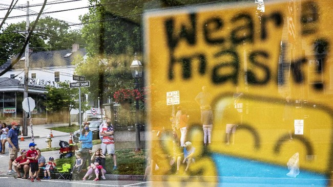 Parade goers are reflected in a storefront window posting a sign for customers to wear face masks before a Fourth of July parade begins Saturday, July 4, 2020, in Bristol, R.I. The town, which lays claim to the nation's oldest Independence Day celebration in the country, held a vehicle-only scaled down version of its annual parade Saturday due to the coronavirus pandemic. (AP Photo/David Goldman)