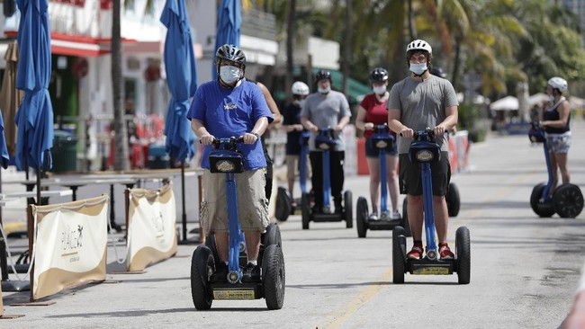 A tour group riding Segways rides down Miami Beach, Florida's famed Ocean Drive on South Beach, July 4, 2020. The Fourth of July holiday weekend began Saturday with some sobering numbers in the Sunshine State: Florida logged a record number of people testing positive for the coronavirus. (AP Photo/Wilfredo Lee)