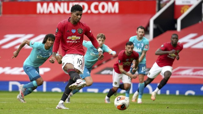 Manchester United's Marcus Rashford scores a penalty kick goal during the English Premier League soccer match between Manchester United and Bournemouth at Old Trafford stadium in Manchester, England, Saturday, July 4, 2020. (Dave Thompson/Pool via AP)