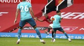 Manchester United's Anthony Martial, center, gets a shot off between Bournemouth's Dominic Solanke (9) and Lloyd Kelly (26) while scoring a goal during the English Premier League soccer match between Manchester United and Bournemouth at Old Trafford stadium in Manchester, England, Saturday, July 4, 2020. (Dave Thompson/Pool via AP)