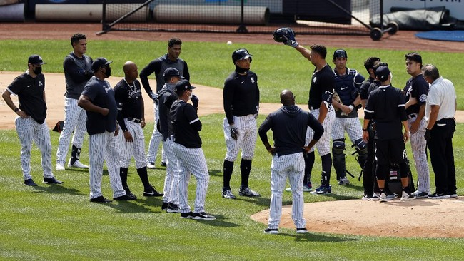 New York Yankees pitcher Masahiro Tanaka, right, is tended to by team medical personnel after being hit by a ball off the bat of Yankees Giancarlo Stanton during a baseball a workout at Yankee Stadium in New York, Saturday, July 4, 2020. (AP Photo/Adam Hunger)