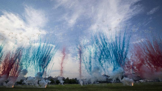 The White House, center, is obscured by Red and Blue smoke from fireworks on the Ellipse during a