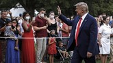 President Donald Trump greets visitors as he walks on the South Lawn of the White House during a