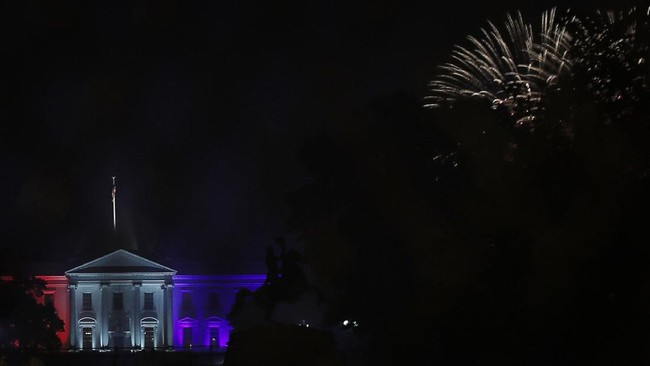 Fireworks burst near the White House, lit in red, white and blue for Independence Day, as seen through a security fence near a section of 16th Street that's been renamed Black Lives Matter Plaza, Saturday, July 4, 2020, in Washington.(AP Photo/Maya Alleruzzo)