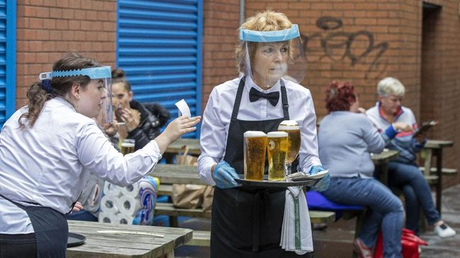 Staff wearing PPE (personal protective equipment) in the form of face shields and gloves serve people enjoying a drink in Belfast city centre on July 3, 2020, as pubs open their doors after the enforced closure due to the coronavirus pandemic. - Pubs, cafes, restaurants and hotels in Northern Ireland are permitted to reopen from Friday as relaxations of the coronavirus restrictions continue. (Photo by Paul Faith / AFP)