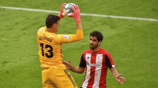 Real Madrid's goalkeeper Thibaut Courtois stops the ball next to Athletic Bilbao's Raul Garcia during the Spanish La Liga soccer match between Athletic Club and Real Madrid at the San Manes stadium in Bilbao, Spain, Sunday, July 5, 2020. (AP Photo/Alvaro Barrientos)