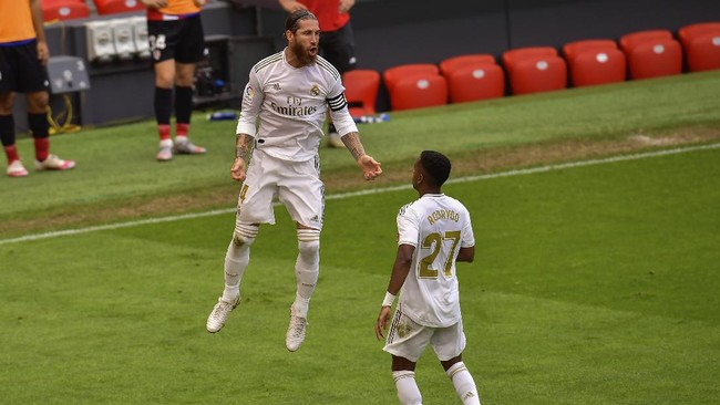 Real Madrid's Sergio Ramos, left, celebrates after scoring the opening goal from a penalty shoot during the Spanish La Liga soccer match between Athletic Club and Real Madrid at the San Manes stadium in Bilbao, Spain, Sunday, July 5, 2020. (AP Photo/Alvaro Barrientos)
