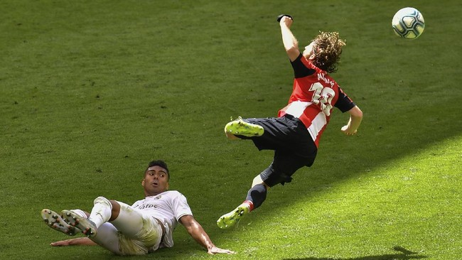 Athletic Bilbao's Iker Muniain is tackled by Real Madrid's Casemiro during the Spanish La Liga soccer match between Athletic Club and Real Madrid at the San Manes stadium in Bilbao, Spain, Sunday, July 5, 2020. (AP Photo/Alvaro Barrientos)