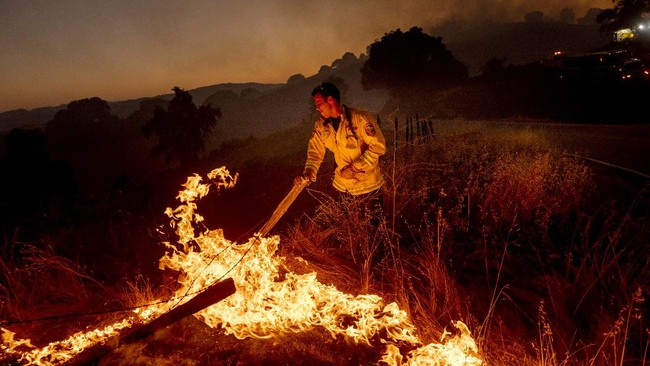 A firefighter moves a fence post while battling the Crews Fire near Gilroy, Calif., on Sunday, July 5, 2020. (AP Photo/Noah Berger)