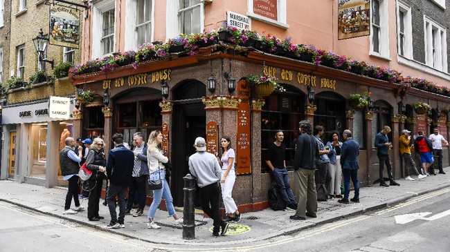 People stand outside a pub in Soho, as the capital is set to reopen after the lockdown due to the Coronavirus outbreak, in London, Saturday, July 4, 2020. England is embarking on perhaps its biggest lockdown easing yet as pubs and restaurants have the right to reopen for the first time in more than three months. In addition to the reopening of much of the hospitality sector, couples can tie the knot once again, while many of those who have had enough of their lockdown hair can finally get a trim. (AP Photo/Alberto Pezzali)