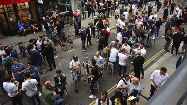 Drinkers in Soho congregate, as coronavirus lockdown restrictions eased across the country, in London, Saturday July 4, 2020. England embarked on perhaps its biggest lockdown easing yet as pubs and restaurants reopened for the first time in more than three months. (Victoria Jones/PA via AP)