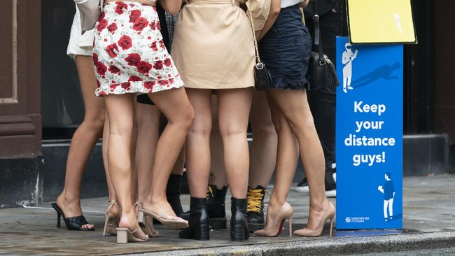 Women are seen outside a bar in Manchester, England, Saturday July 4, 2020. England is embarking on perhaps its biggest lockdown easing yet as pubs and restaurants have the right to reopen for the first time in more than three months. In addition to the reopening of much of the hospitality sector, couples can tie the knot once again, while many of those who have had enough of their lockdown hair can finally get a trim. (AP Photo/Jon Super)