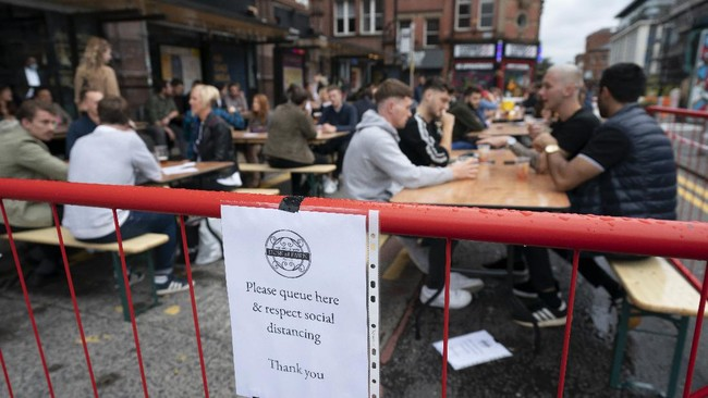 Members of the public are seen at a bar in Manchester's Northern Quarter, England, Saturday July 4, 2020. England is embarking on perhaps its biggest lockdown easing yet as pubs and restaurants have the right to reopen for the first time in more than three months. In addition to the reopening of much of the hospitality sector, couples can tie the knot once again, while many of those who have had enough of their lockdown hair can finally get a trim. (AP Photo/Jon Super)