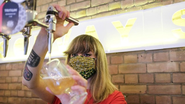 A member of staff at Solvay Society brewery in Leytonstone pours a beer on the first day of reopening after the lockdown due to the Coronavirus outbreak, in London, Saturday, July 4, 2020. England is embarking on perhaps its biggest lockdown easing yet as pubs and restaurants have the right to reopen for the first time in more than three months. In addition to the reopening of much of the hospitality sector, couples can tie the knot once again, while many of those who have had enough of their lockdown hair can finally get a trim. (AP Photo/Alberto Pezzali)