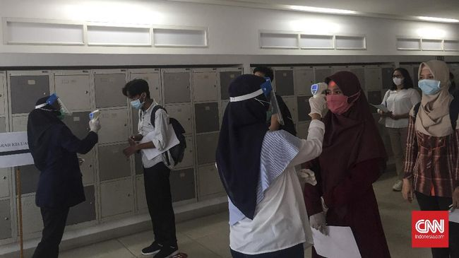 Peserta Seleksi Bersama Masuk Perguruan Tinggi Negeri berbaris dan melakukan pemeriksaan suhu sebelum memasuki ruang Ujian Tes Berbasis Komputer di Universitas Indonesia, Senin (6/7).