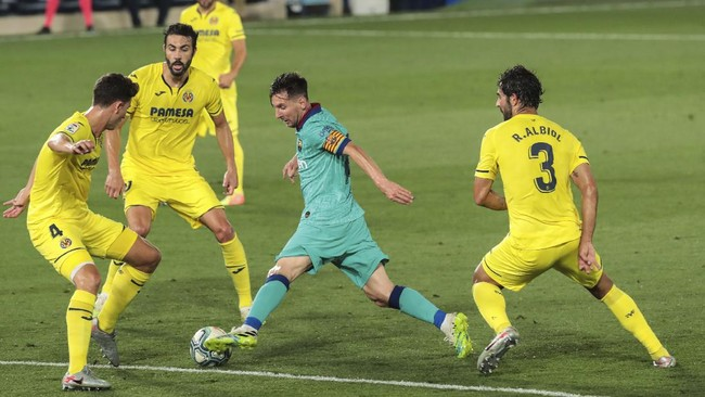 FC Barcelona's Lionel Messi, second right, duels for the ball with Villareal's Pau Torres, left, and Villareal's Raul Albiol, right, during the Spanish La Liga soccer match between FC Barcelona and Villareal at La Ceramica stadium in Villareal, Spain, Sunday, July 5, 2020. (AP Photo/Jose Miguel Fernandez de Velasco)