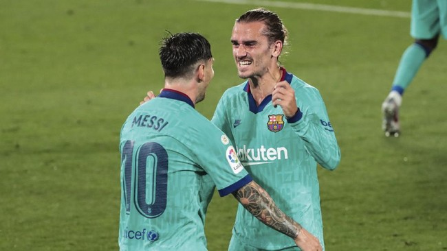 Barcelona's Antoine Griezmann, right, is congratulated by teammate Lionel Messi after scoring his side third goal during the Spanish La Liga soccer match between FC Barcelona and Villareal at La Ceramica stadium in Villareal, Spain, Sunday, July 5, 2020. (AP Photo/Jose Miguel Fernandez)