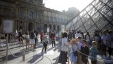 Visitors wait in the Louvre Museum courtyard prior to visit the museum, in Paris, Monday, July 6, 2020. The home of the world's most famous portrait, the Louvre Museum in Paris, reopened Monday after a four-month coronavirus lockdown. (AP Photo/ Thibault Camus)