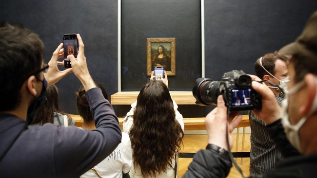 Visitors take photos of the Leonardo da Vinci's painting Mona Lisa, in Paris, Monday, July 6, 2020. The home of the world's most famous portrait, the Louvre Museum in Paris, reopened Monday after a four-month coronavirus lockdown. (AP Photo/ Thibault Camus)