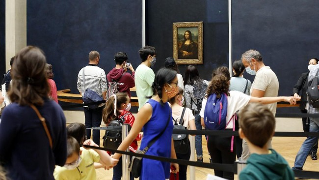 Visitors wait to see the Leonardo da Vinci's painting Mona Lisa, in Paris, Monday, July 6, 2020. The home of the world's most famous portrait, the Louvre Museum in Paris, reopened Monday after a four-month coronavirus lockdown. (AP Photo/ Thibault Camus)