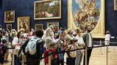 Visitors watch the Leonardo da Vinci's painting Mona Lisa, in Paris, Monday, July 6, 2020. The home of the world's most famous portrait, the Louvre Museum in Paris, reopened Monday after a four-month coronavirus lockdown. (AP Photo/ Thibault Camus)