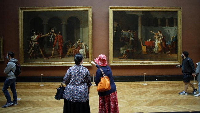 Visitors watch oil on canvas entitled Le serment des Horaces, left, and Licteurs rapportant à Brutus le corps de ses fils, by Jacques Louis David in the Louvre Museum, in Paris, Monday, July 6, 2020. The home of the world's most famous portrait, the Louvre Museum in Paris, reopened Monday after a four-month coronavirus lockdown. (AP Photo/ Thibault Camus)