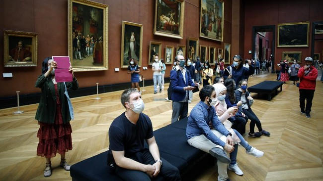 Visitors watch oil on canvas of 1807 entitled Le Sacre de Napoleon by Jacques Louis David, at the Louvre Museum, in Paris, Monday, July 6, 2020. The home of the world's most famous portrait, the Louvre Museum in Paris, reopened Monday after a four-month coronavirus lockdown. (AP Photo/ Thibault Camus)