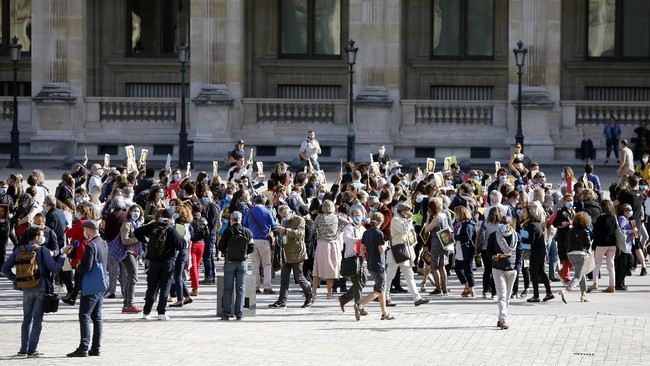 Guide speakers demonstrate to warn about their financial situation in front of the Louvre Museum, in Paris, Monday, July 6, 2020. The home of the world's most famous portrait, the Louvre Museum in Paris, reopened Monday after a four-month coronavirus lockdown. (AP Photo/ Thibault Camus)