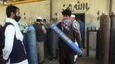 A man carries an oxygen tank from a privately owned oxygen factory, in Kabul, Afghanistan, Thursday June 18, 2020. For seven years, Najibullah Seddiqi's oxygen factory sat idle in the Afghan capital Kabul. He shut it down, he says, because corruption and power cuts made it impossible to work. But when the novel coronavirus began racing through his country, he opened the factory's dusty gates and went back to work. Now he refills hundreds of oxygen cylinders a day for free for COVID-19 patients — and at reduced rates for hospitals. (AP Photo/Rahmat Gul)