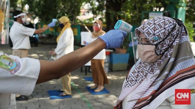 Sejumlah pengajar SDN Pekayon Jaya VI Bekasi melakukan simulasi tahun ajaran baru. Sebelum masuk halaman sekolah, siswa diwajibkan memeriksa suhu tubuh. CNN Indonesia/Safir Makki