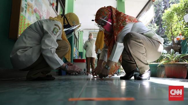 Pengajar memberi batas untuk siswa Yang Akan masuk kelas. CNN Indonesia/Safir Makki