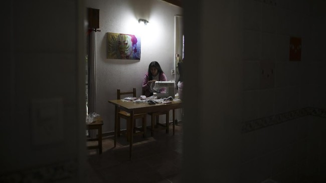 Tatiana Fronti works at her sewing machine during a government-ordered lockdown to curb the spread of the new coronavirus in Buenos Aires, Argentina, Friday, June 26, 2020. The 29-year-old textile designer separated from her decade-long partner days before the quarantine started, and had to cancel her trip to the U.S. to see her favorite singer, Lady Gaga. Instead of getting depressed, she redecorated her house, passed four subjects in an online business administration course, and focused on her underwear brand TIEF, and is seeing sales rise. (AP Photo/Natacha Pisarenko)