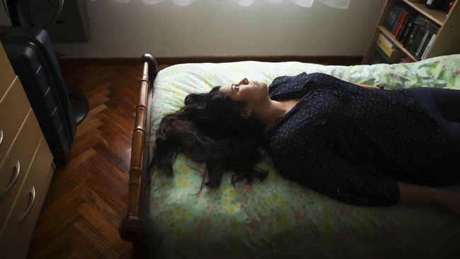 Camila Fernandez poses for a photo on her bed during a government-ordered lockdown to curb the spread of the new coronavirus in Buenos Aires, Argentina, Monday, June 29, 2020. The 26-year-old who works at the prosecutor's office lives alone in her apartment in the company of books, of which she has read more than 20 during quarantine, while studying to become a public translator and English teacher.