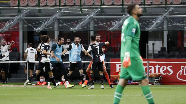 Juventus' Cristiano Ronaldo, right, celebrates with his teammates his goal against AC Milan as AC Milan's goalkeeper Gianluigi Donnarumma walks during the Serie A soccer match between AC Milan and Juventus at the San Siro stadium, in Milan, Italy, Tuesday, July 7, 2020. (AP Photo/Antonio Calanni)