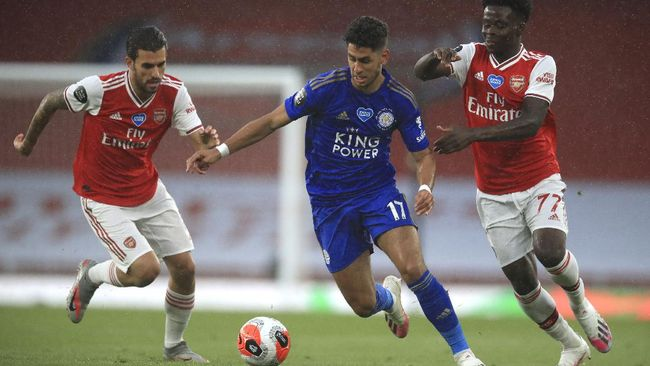 Leicester's Ayoze Perez, centre, takes the bad past Arsenal's Dani Ceballos, left, and Arsenal's Bukayo Saka, right, during the English Premier League soccer match between Arsenal and Leicester at Emirates Stadium in London, England, Tuesday, July 7, 2020. (AP Photo/Adam Davy,Pool)