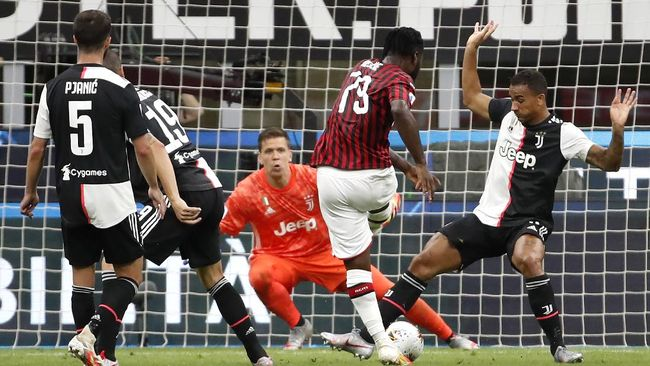 AC Milan's Franck Kessie, center, scores against Juventus during the Serie A soccer match between AC Milan and Juventus at the San Siro stadium, in Milan, Italy, Tuesday, July 7, 2020. (AP Photo/Antonio Calanni)