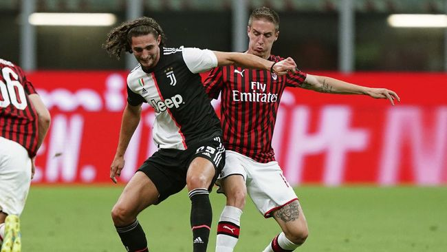AC Milan's Andrea Conti, right, and Juventus' Adrien Rabiot vie for the ball during the Serie A soccer match between AC Milan and Juventus at the Milan San Siro Stadium, Italy, Tuesday, July 7, 2020. (Spada/LaPresse via AP)