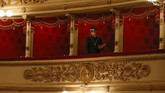 A usher wearing a mask looks down prior to a show at the La Scala theater in Milan Italy, Monday, July 6, 2020. La Scala opera house reopened Monday after a four-month shutdown due to the COVID-19 restriction measures. (AP Photo/Antonio Calanni)