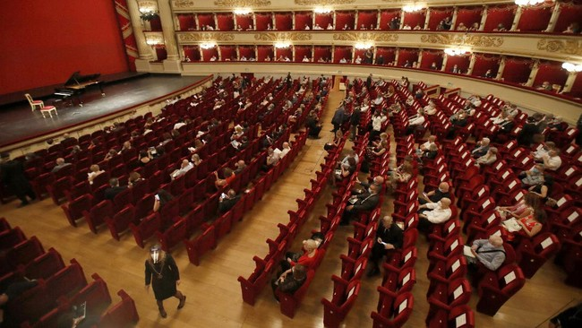Spectators sit apart from each other to respect social distancing, prior to a show at the La Scala theater in Milan Italy, Monday, July 6, 2020. La Scala opera house reopened Monday after a four-month shutdown due to the COVID-19 restriction measures. (AP Photo/Antonio Calanni)