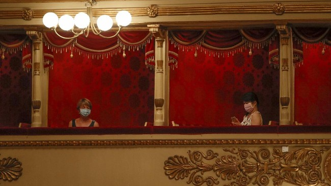 Spectators wearing masks sit prior to a show at the La Scala theater in Milan Italy, Monday, July 6, 2020. La Scala opera house reopened Monday after a four-month shutdown due to the COVID-19 restriction measures. (AP Photo/Antonio Calanni)