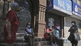 Women wait for their appointments outside of a nail salon in the Harlem section of New York, Monday, July 6, 2020. Nail salons and dog runs were back in business on Monday as New York City entered a new phase in the easing of coronavirus restrictions, but indoor restaurant dining will be postponed indefinitely in order to prevent a spike in new infections. (AP Photo/Seth Wenig)