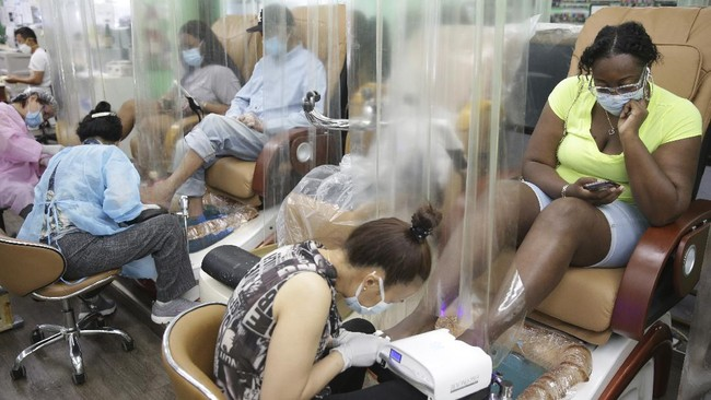 Candace Sanders, right, sits behind a plastic curtain while getting a pedicure at HT&V Nails in the Harlem section of New York, Monday, July 6, 2020. Nail salons and dog runs were back in business on Monday as New York City entered a new phase in the easing of coronavirus restrictions, but indoor restaurant dining will be postponed indefinitely in order to prevent a spike in new infections. (AP Photo/Seth Wenig)