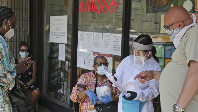 People try to figure out whose appointment is next while talking to an employee in front of HT&V Nails in the Harlem section of New York, Monday, July 6, 2020. Nail salons and dog runs were back in business on Monday as New York City entered a new phase in the easing of coronavirus restrictions, but indoor restaurant dining will be postponed indefinitely in order to prevent a spike in new infections. (AP Photo/Seth Wenig)