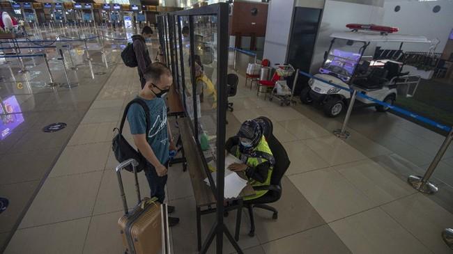 Calon penumpang menyerahkan dokumen hasil tes rapid negatif COVID-19 kepada petugas di Terminal 3 Bandara Internasional Soekarno-Hatta, Tangerang, Banten, Kamis (9/7/2020). Meski penerbangan telah kembali dibuka dengan persyaratan  seperti penumpang harus dengan memiliki hasil rapid atau PCR test negatif COVID-19, suasana di Bandara Soekarno Hatta masih terpantau sepi. ANTARA FOTO/Aditya Pradana Putra/aww.