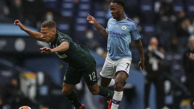 Newcastle's Dwight Gayle, left, is tackled by Manchester City's Raheem Sterling during the English Premier League soccer match between Manchester City and Newcastle at the Ethiad Stadium in Manchester, England, Wednesday, July 8, 2020. (Lee Smith/Pool via AP)