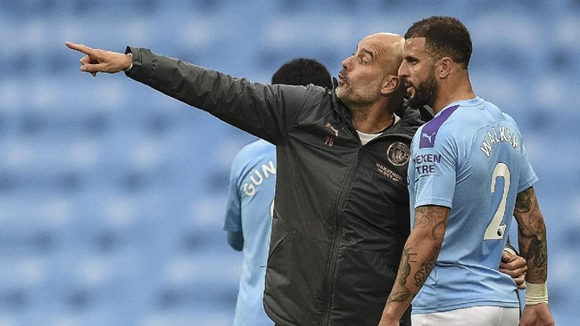 Manchester City's head coach Pep Guardiola, left, talks with Manchester City's Kyle Walker during the English Premier League soccer match between Manchester City and Newcastle at the Ethiad Stadium in Manchester, England, Wednesday, July 8, 2020. (Oli Scarff/Pool via AP)