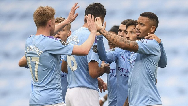 Manchester City players celebrate after scoring the opening goal during the English Premier League soccer match between Manchester City and Newcastle at the Ethiad Stadium in Manchester, England, Wednesday, July 8, 2020. (Michael Regan/Pool via AP)